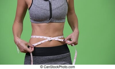 Young woman measuring her fit and healthy body - Studio shot...
