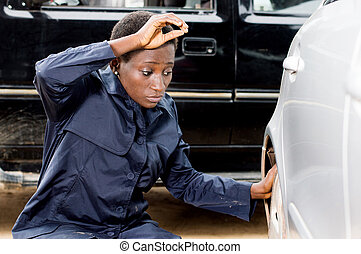 Young woman mechanic changing a tire of a car.