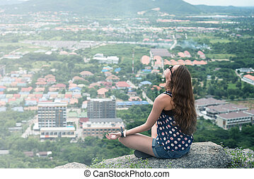 Young woman meditate on the top of mountain background with Hua