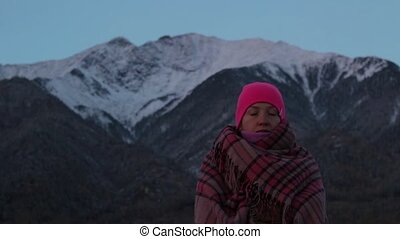 Young woman meditates at the foot of the mountains.
