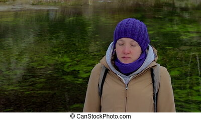 Young woman meditates on a background of green lake