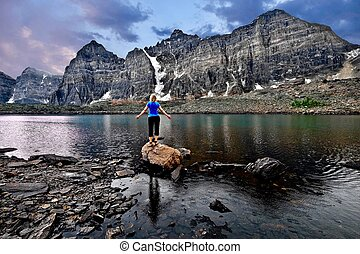 Young woman meditating by lake in Valley of Ten Peaks. Eifel Lake in Banff National Park.