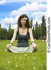 Young woman meditating in a park