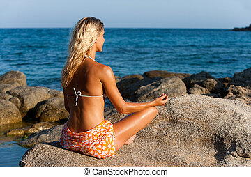 Young woman meditating in late afternoon sun.