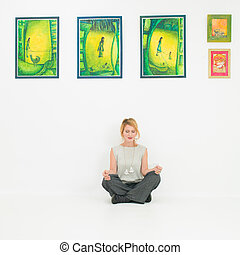 young woman meditating in lotus position in museum