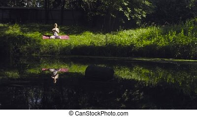 Young woman meditating in the park - Young attractive woman...