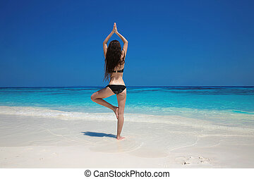 Young Woman meditating in tree yoga position on the exotic beach. Zen, meditation, peace. Balance. Bliss freedom concept.