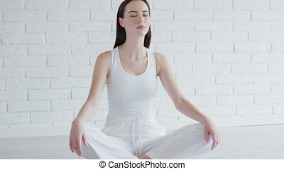 Young woman meditating in white room - Pretty young female...