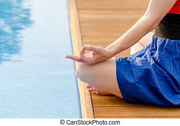 Young woman meditating on a wooden deck