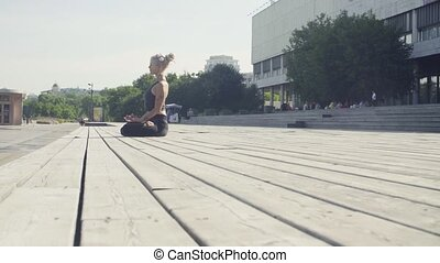 Young woman meditating outdoors at summer day