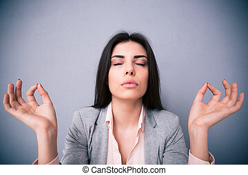 Young woman meditating over gray background