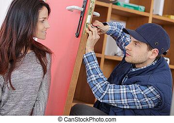 young woman meeting smiling service worker fixing her door