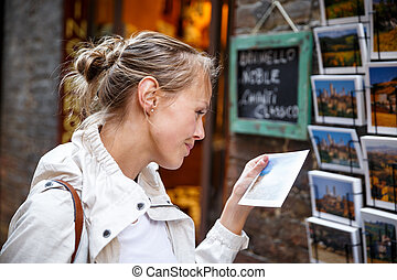 Young woman messaging/using app on her smart-phone in a city street context