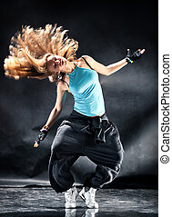 Young woman modern dance. Dark grungy background.