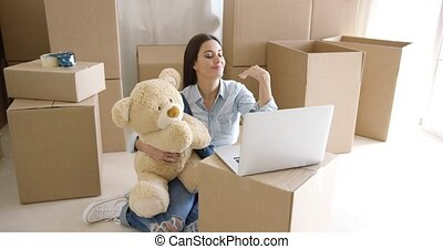 Young woman moving house with her teddy bear - Young woman...