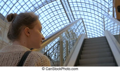 Young woman moving on escalator and looking around in mall