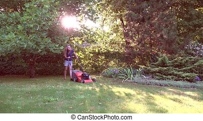 Young woman mowing the grass during the beautiful evening...