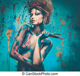 Young woman muse with creative body art and hairdo holding...