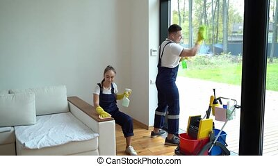 young woman nd man from cleaning service dressed in workwear...