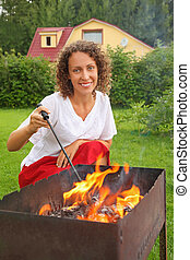 young woman near brazier on picnic