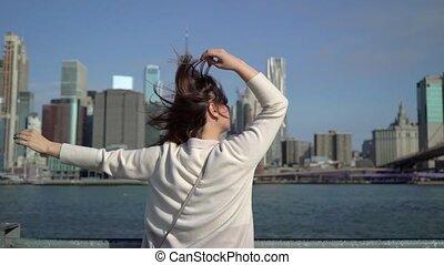 Young woman near Brooklyn bridge embankment walking