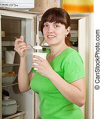 woman near opening fridge eating yoghurt