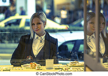 Young woman near shop window with jewels.