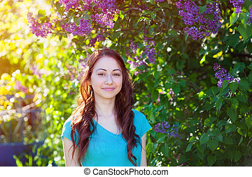 young woman near the lilac bush in the spring park