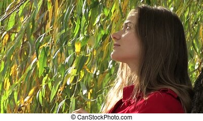 Young woman near willow tree