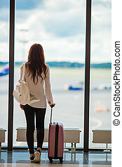 Young woman near window in an airport lounge waiting for arrive