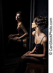 Young woman next to a mirror