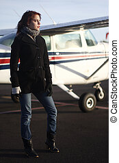 Young woman next to airplane