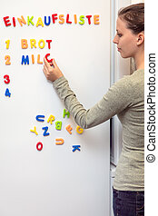 young woman notes the shopping list on the fridge with colorful magnet letters