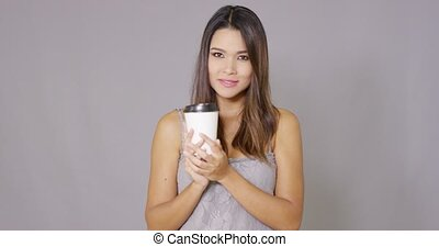 Young woman offering a cup of takeaway coffee holding out...