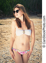 Young woman on a beach in bikini