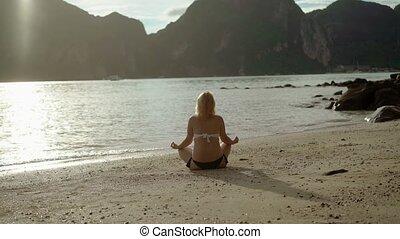 Young woman on a beach practise yoga in bikini
