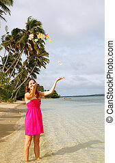 Young woman on a beach throwing flowers in the air