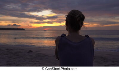 Young woman on a beach watching a fantastic sunset