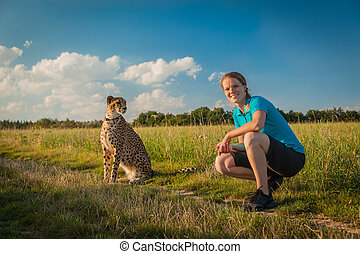Young woman on a green meadow in summer walking cheetah
