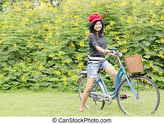 Young woman on a green meadow with a bicycle