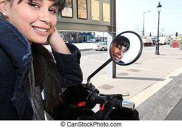 Young woman on a moped in  town