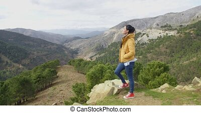 Young woman on a mountain plateau standing with her foot on...