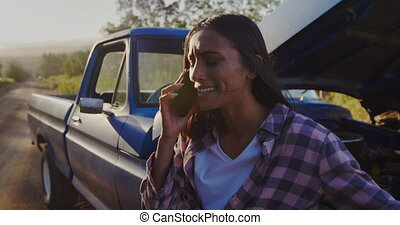 Young woman on a road trip in pick-up truck - Side view of a...