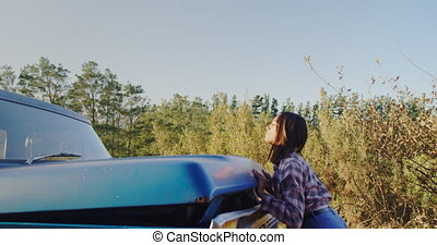 Young woman on a road trip next to pick-up truck - Side view...