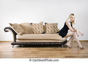 Blond girl sits on the sofa against the background of the white wall