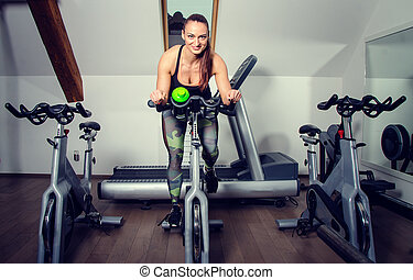 Young woman on a spinning bicycle.