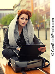 Young woman on a street bench with laptop