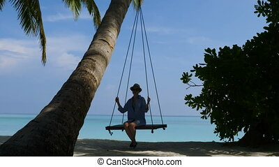Young woman on a swing with a phone. Beautiful beach and ocean.