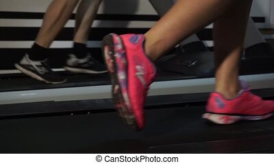 Young woman on a treadmill close-up in the gym