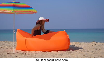 Young woman on a tropical beach laying down on an inflatable...